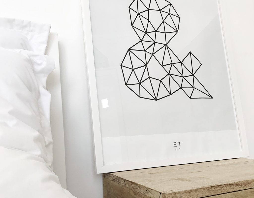 minimal picture of a designed frame on a nightstand next to a bed